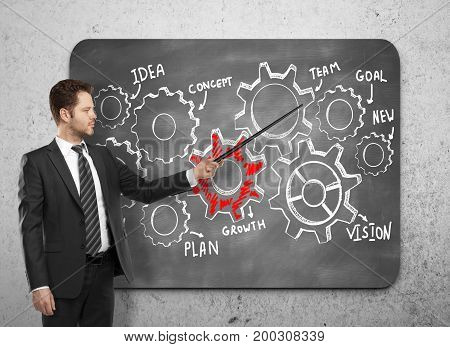 Handsome european businessman pointing at cogwheels drawn on chalkboard. Presentation and teamwork concept