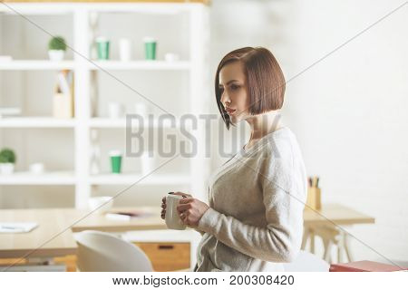 Portrait of beautiful european woman drinking coffee or tea while standing in modern office with items on shelves. Morning breakfast break energy boost concept