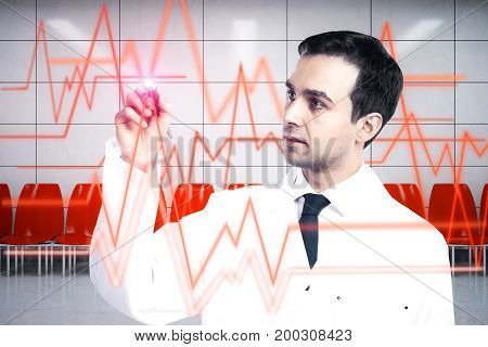 Young male doctor drawing abstract heartbeat line on interior background. Cardiology concept