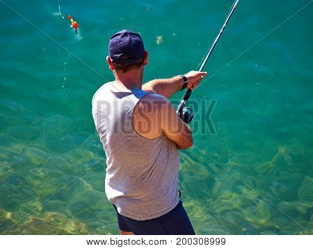Great leisure activity - Man fishing by the ocean sea