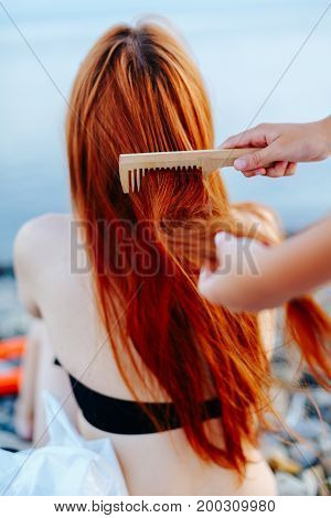 Back view of redhead woman in swimsuit sitting on beach and being brushed by anonymous person.