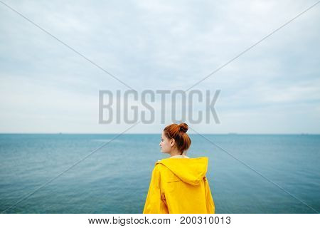 Back view of redhead woman in yellow raincoat looking away on background of blue ocean.