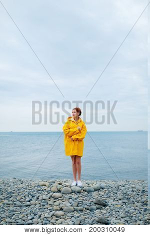 Portrait of young woman wearing bright yellow raincoat on background of ocean.