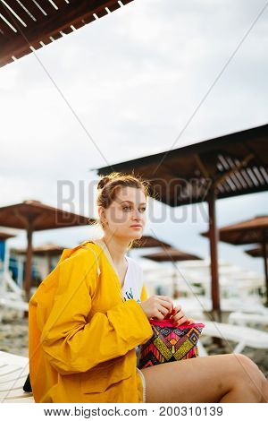Young woman in bright raincoat sitting on sunbed on pebble beach.