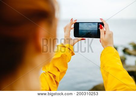 Young redhead woman in yellow raincoat posing on coastline of ocean taking photo of nature with smartphone.