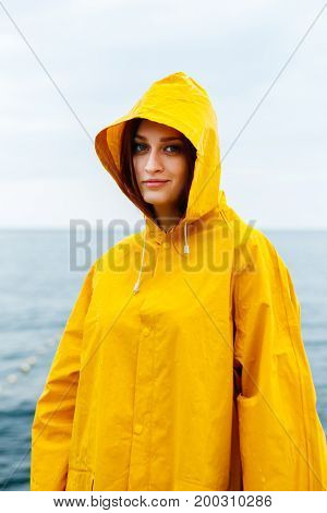 Portrait of young woman wearing bright yellow raincoat and looking at camera on background of ocean.