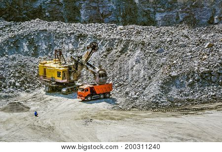 Huge excavator truck and man standing next on granite quarry. Yellow carver machine excavator stonecutter for industrial granite stands in a quarry near granite stones