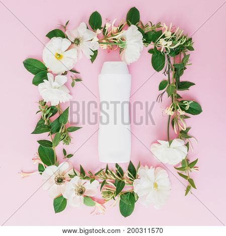 Floral frame of white flowers and shampoo or gel in white package on pink background. Floral background. Flat lay, top view.