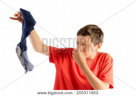 Young teenage boy isolated on a white background holding a smelly sock