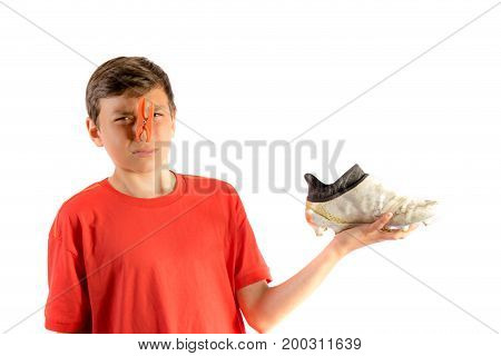 Young teenage boy isolated on a white background with a smelly football boot