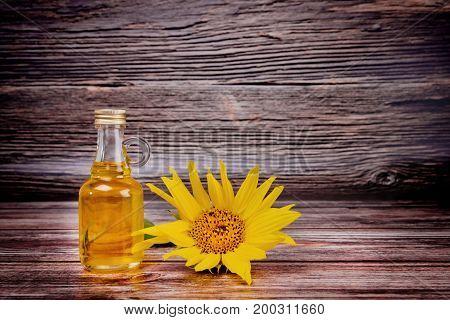 Glass Bottle With Sunflower Oil And Sunflower Flower On Wooden Background. Studio Shot.