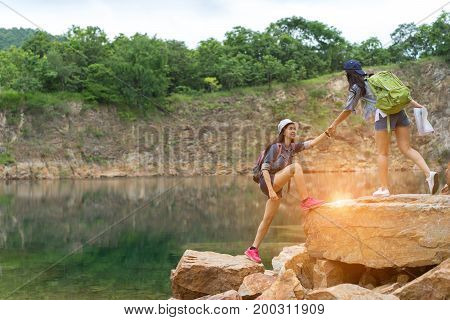 Young girl asian help friend together hiking with backpack holding hand climbing on the mountain success finish in travel trip adventure.