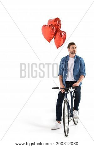 handsome man with bicycle and red heart shaped balloons isolated on white