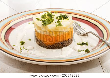 haggis a very scottish dish with mashed potato turnips and parsley on a plate