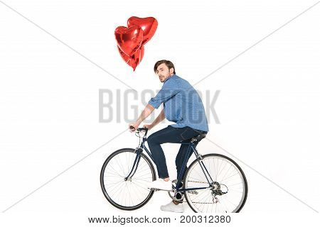 young man riding bicycle with heart shaped balloons isolated on white