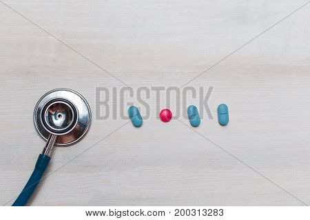 Stethoscope And The Drug Tablet On White Wooden Background Top View.