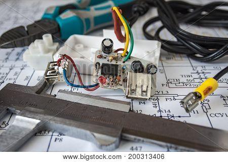 male repairman checking fridge with digital multimeter at home