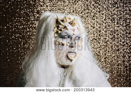 Mystery and fantasy concept. Monster with thorns and warts on face. Man with grey beard and dragon skin. Demon in white cloth on golden bokeh background. Wizard with long silver hair.