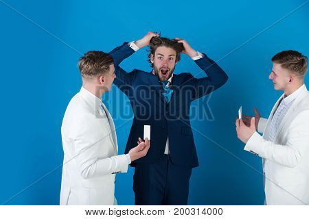 Man shocked shouting and pulling hair on blue background. Two businessmen showing visiting and bank cards. Stress and frustration. Business problem and solution concept.