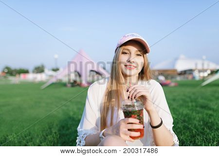Portrait of a beautiful smiling girl with a refreshing drink in her arms resting in the park. Summer concept