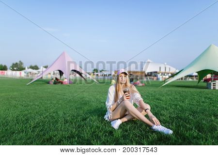 Portrait of a positive girl who has a rest in a beautiful park on a green lawn and drinks a refreshing drink.