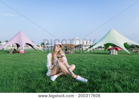 Smiling beautiful young woman sitting on a gonzone in a recreation park with mojito in her arms and resting. Summer concept