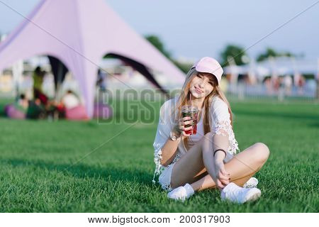 Portrait of a smiling girl resting on a green lawn and drinking cold lemonade. Summer concept. Rest in the park