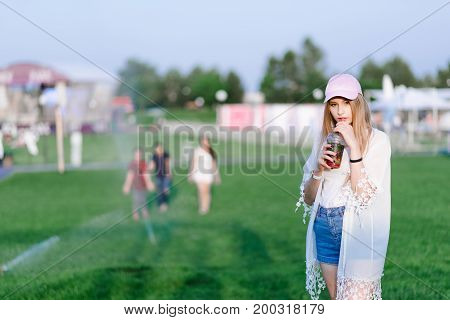Stylish young and beautiful girl stands with a strawberry lemonade in her hand against the backdrop of a relaxation park. Summer concept. Rest in the park.