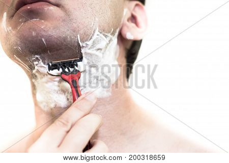 A man is shaving a machine a cheek in foam close-up. Bristles on face. No beard. The face is not visible.