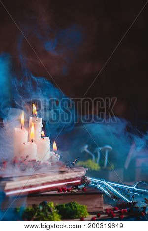 Burning white candles with rising smoke in a magical still life with books, notes, potion bottles, moss and mushrooms. Dark enchanted scene. Copy space.