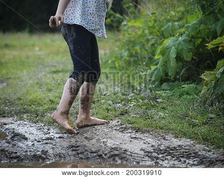 Child's feet covered with dirt. Green grass dirt
