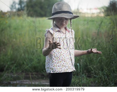 Child surprised considering dirty hands. The girl in the hat. Field rural nature
