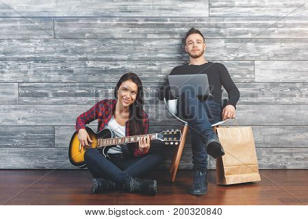 Happy friends playing the guitar having fun and communication at home in wooden interior. Reunion concept