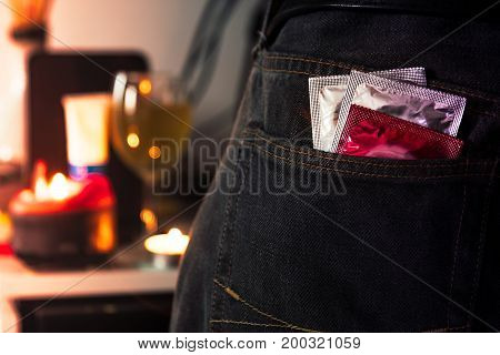 Condoms in package in jeans with blurred party background. Protection against AIDS. Safe sex concept. contraception and birth control. Protection against unwanted pregnancy.