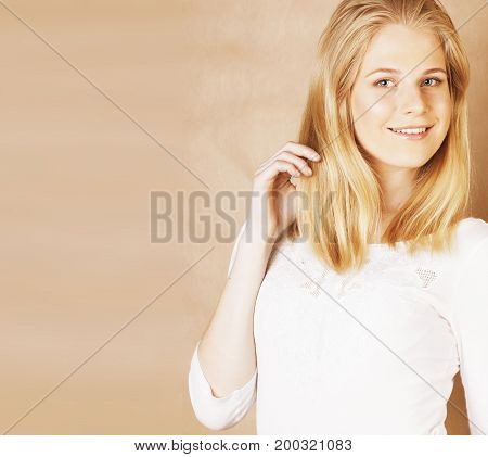 young cool blong teenage girl messed with her hair smiling close up on warm brown background, lifestyle real people concept