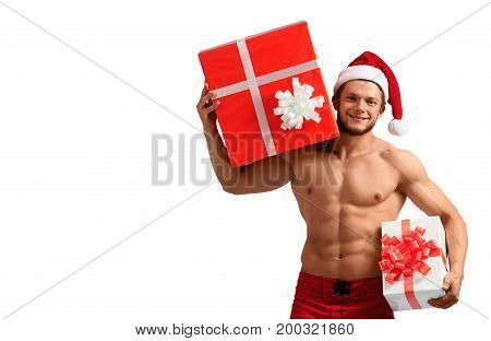 You gonna love it. Young naked man with abs wearing Santa Claus hat holding presents on white background with a copyspace on the side
