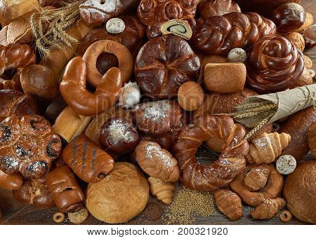 Top view shot of delicious sweet rolls and different kinds of freshly baked bread piled on the table copyspace bakery cooking deli concept.