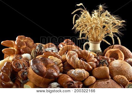 Tasty sweet rolls and various breads piled on the table on grey background copyspace kitchen bakery food eating wheat organic concept.