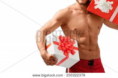 I know what to ask for Christmas. Cropped closeup studio shot of an astonishing muscular naked man with presents in his hands