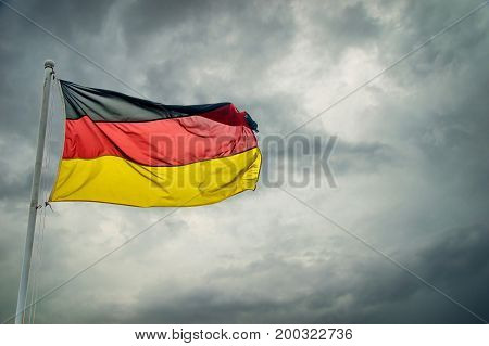 A German flag in front of dark clouds background