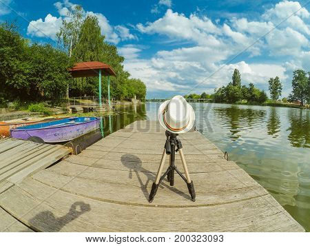 A tripod covered with a hat on the Wooden surface of the pier dock on river lake with a cloudy sky on a sunny summer day. Concept of rest holiday.