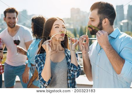 Group of people having barbecue party playing with food