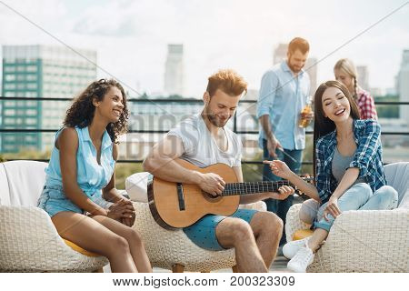 Group of people having barbecue party playing guitar