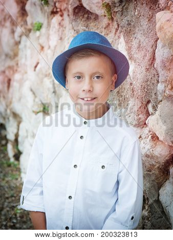 Cute little boy with a hat on a background of nature
