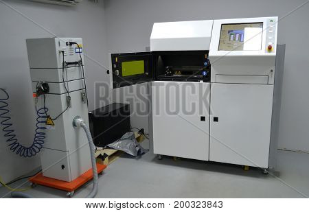 Laser sintering machine for metal. Open working chamber of a laser sintering machine for metal. Overall plan. 3D printer printing metal. Modern additive technologies 4.0 industrial revolution
