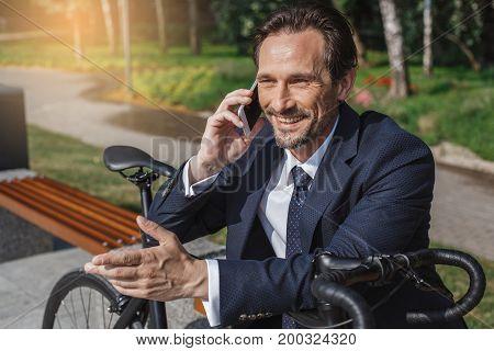 Senior businessman with a bike outside phone call
