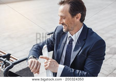 Senior businessman with a bike outside checking time