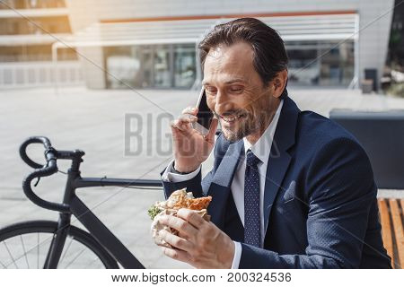 Senior businessman with a bike outside eating lunch