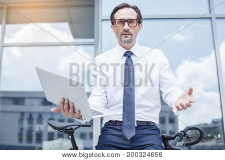 Senior businessman with a bike outside u