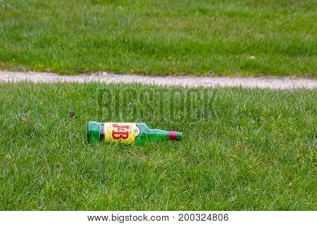 PARIS/FRANCE - MARCH 31, 2013: Empty bottle J&B on grass in Paris at Champ de Mars